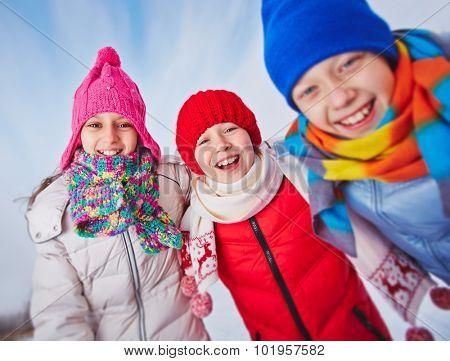 Laughing kids in winterwear looking at camera