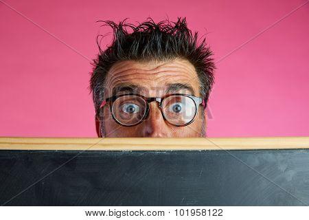 Nerd man crazy behind a blackboard funny gesture in pink background
