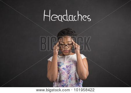 African Woman With Fingers On Temples With A Headache On Blackboard Background