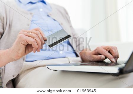 technology, age and people concept - close up of senior woman with laptop compute and credit or bank card r at home