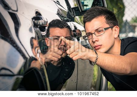 Young Man With Glasses Inspecting A Luxury Car Before A Second Hand Trade