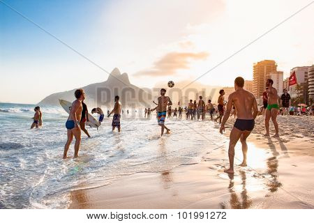 RIO DE JANEIRO, BRAZIL - APRIL 24, 2015: Carioca Brazilians playing altinho futebol beach football kicking soccer balls at sunset Ipanema Beach on April 24, 2015, Rio de Janeiro. Brazil.