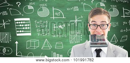 Geeky smiling businessman biting calculator against green chalkboard