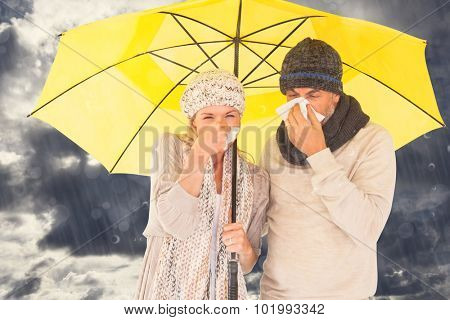 Couple sneezing in tissue while standing under umbrella against blue sky with white clouds