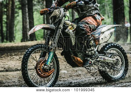 Motocross driver on muddy offroad track