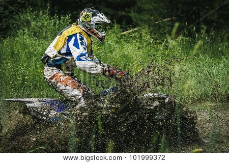 Motocross driver under the spray of mud