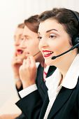Group of three customer care representatives in a call center with headphones poster