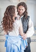 Handsome man in medieval costume undress beautiful woman with long hair poster