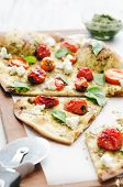 Gourmet thin crust pizza with roasted tomatoes, fresh basil and feta cheese poster