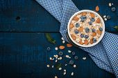 A healthy breakfast on a dark blue wooden background: Oatmeal, milk, blueberries, honey and almonds. Rustic style. poster