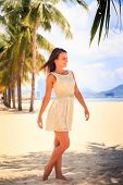 european brunette slim girl in short white lace frock barefoot poses and smiles on sand beach against row of palms poster