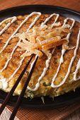 Japanese pizza: okonomiyaki on a plate close-up and chopsticks. Vertical poster