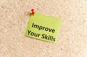 improve your skills word typed on a paper and pinned to a cork notice board poster