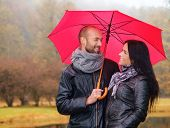 Happy middle-aged couple with umbrella outdoors on beautiful rainy autumn day poster