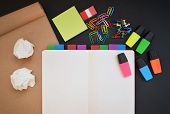 Creative workspace with open notebook, craft paper, colorful highlighters, clips and pins on black desk poster