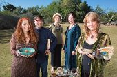 Five smiling Wicca practitioners standing outdoors with smudge stick poster