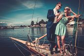 Stylish wealthy couple on a luxury yacht  poster