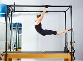 Pilates woman in cadillac acrobatic reformer exercise at gym poster