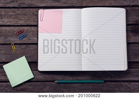 Overhead of diary, sticky notes, pencil and paper clip on wooden table
