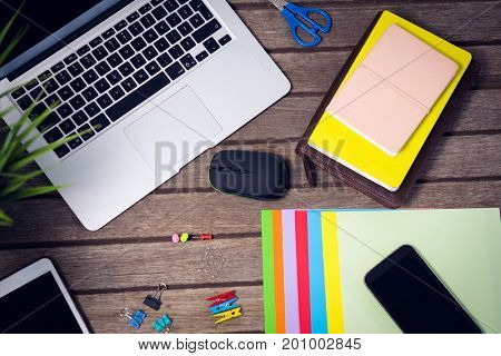 Laptop and digital tablet with office supplies on wooden table