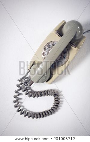 Overhead view of landline phone on white table