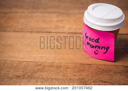 Close up of good morning text stuck on disposable cup at wooden table