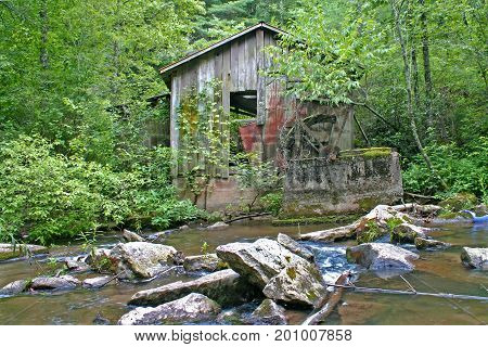 an old, dilapidated gristmill at the edge of the woods by a stream