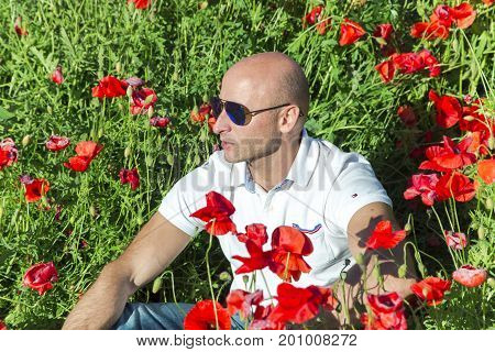Portrait of men in sunglasses against a background of red poppies in the height of summer.Businessman resting on nature and enjoying the bright red wild flowers, harmony concept.