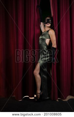 Female artist in masquerade mask posing in front of massive red stage curtain