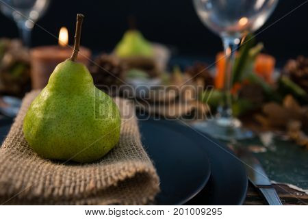 Close up pf pear served on burlap in plate at tabe