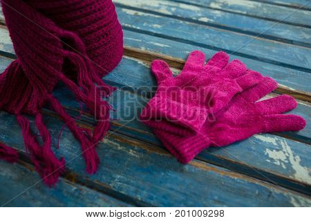 High angle view of pink muffler with gloves on wooden table