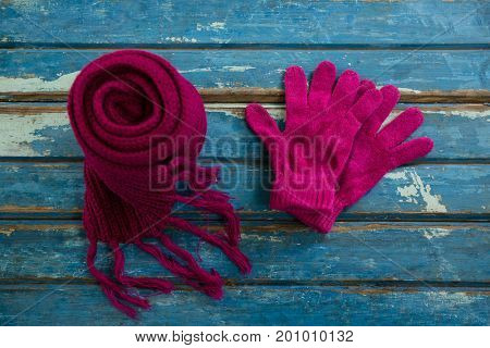 High angle view of muffler with gloves on wooden table