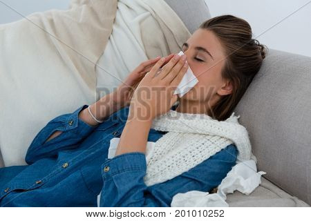 Young woman rubbing nose while lying on sofa at home