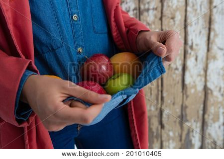 Mid section of woman carrying fruits carrying in shirt while standing against wall