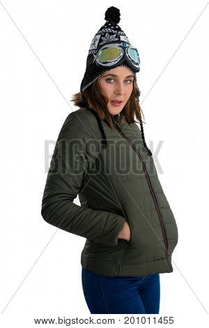 Portrait of woman wearing winter coat while standing with hands in pockets against white background