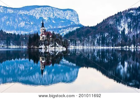 Early morning on the lake Bled and reflection of a church on small island in slovenian alps, Slovenia