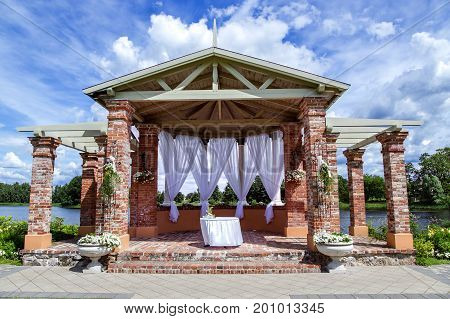 Brick arbour with white light curtains for ceremonies ashore lake in Birini Castle, Latvia