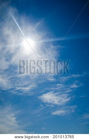 bright blue sky with the sun causing lens flare. Glare from the bright sun in a clear blue sky with a little cloudiness and the effect of vignetting
