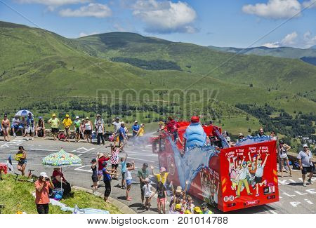 Col de PeyresourdeFrance- July 23 2014: Spectators refreshing under the water spray produced by Vittel vehicle during the passing of the Publicity Caravan on the road to Col de Peyresourde in Pyrenees Mountains in the stage 17 of Le Tour de France 2014.
