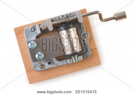 Vintage mechanical music box on a little wooden plank isolated on white background top view.