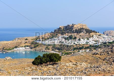 Panoramic view on Lindos town with a beautiful lagoon and ancient fortress on a hill at Rhodes island, Greece