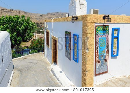 LINDOS, GREECE - AUGUST 2017: Beautiful white building of tavern - souvenir shop in Lindos town on Rhodes island