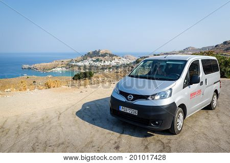 LINDOS, RHODES - AUGUST 2017:Rental Nissan Evalia is staying parked near Lindos town on Rhodes town, Greece