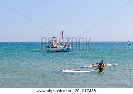 RHODES, GREECE - AUGUST 2017: Windsurfer and fishing boat near coast of Rhodes island.