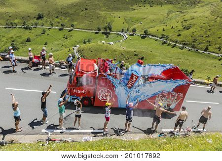 Col de PeyresourdeFrance- July 23 2014: Spectators refreshing under the water spray produced by Vittel vehicle during the passing of the Publicity Caravan on the road to Col de Peyresourde in Pyrenees Mountains in the stage 17 of Le Tour de France 2014