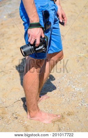 Barefoot photographer in blue shorts on a sandy beach. DSLR camera in hand in sea beach background