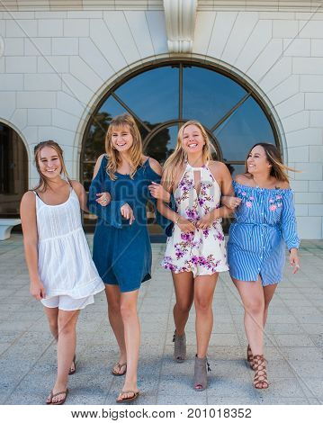 Pretty college girls together in a group walking in white brick courtyard with arms linked.