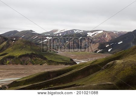 Dramatic Iceland Scenery With Snowy Glacier On The Horizon And Green Mountains Covered With Thick Ic