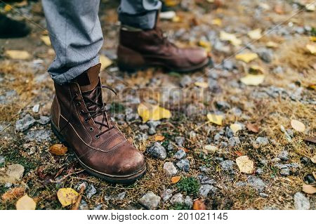 A pair of brown hiking boot in autumn forest. Soft focus on boot. Artwork
