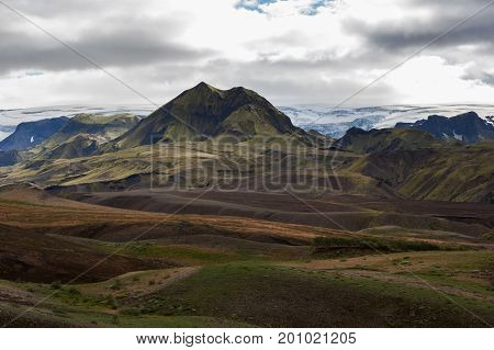 Melancholic Iceland Scenery With Snowy Glacier On The Horizon And Green Mountains Covered With Thick